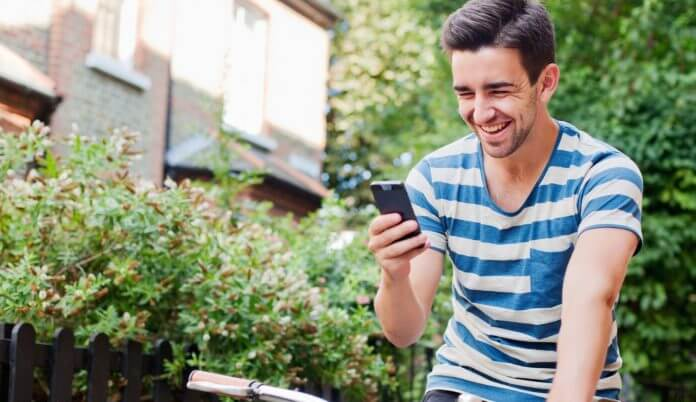 Young man using smart phone on bike